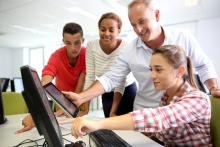 students and teacher working together at a computer