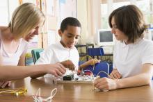 teachers helping a student with a science project