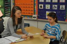 Teacher working at table with student