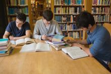 Three students doing school work in the library