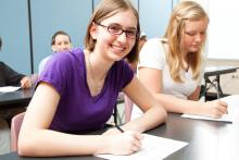 Students taking notes in class at their desks.