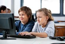 two students sitting at a computer