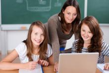 teacher working with students at laptop